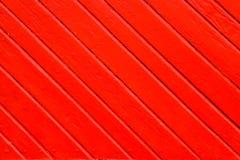 老脏和被风化的红色桔子绘了在对角线的木墙壁板条对框架作为简单的饱和的背景纹理 免版税库存图片