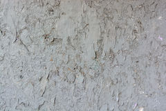 老膏药墙壁表面上的灰色破裂的绘画 图库摄影