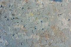 老膏药墙壁表面上的灰色破裂的绘画 免版税库存图片