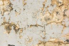 老膏药墙壁表面上的米黄破裂的绘画 库存图片