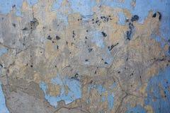 老膏药墙壁表面上的蓝色破裂的绘画 库存照片