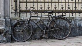 老自行车停放了反对篱芭和一个老房子 免版税库存图片
