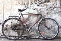 老自行车在大厦附近站立 免版税库存照片