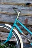 老自行车在木墙壁附近站立 免版税库存图片