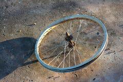 老自行车的金属轮子有阴影的在水泥地面 库存图片