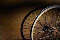 老自行车的金属轮子有阴影的在金属盘区a 免版税库存照片