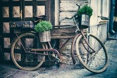 老自行车运载的花盆和手提箱 免版税图库摄影