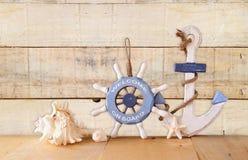 老船舶木轮子、船锚和壳在木桌上在木背景 葡萄酒被过滤的图象 免版税库存照片
