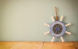 老船舶木轮子、船锚和壳在木桌上在木背景 葡萄酒被过滤的图象 图库摄影