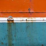 老船船身生锈的金属弓在橙色蓝色的和白色 免版税库存照片
