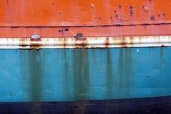 老船船身生锈的金属弓在橙色蓝色的和白色 免版税库存图片