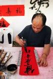 老艺术家在农历新年写着中国象形文字 曼谷泰国 库存照片