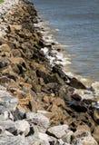 老花岗岩石头防波堤 库存照片