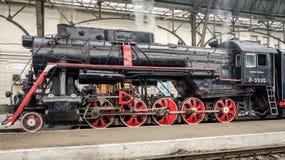 老苏联有一个红色星的葡萄酒黑色减速火箭的火车在火车站在利沃夫州由管子和passeng生产蒸汽 免版税库存照片