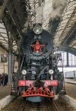老苏联有一个红色星的葡萄酒黑色减速火箭的火车在火车站在利沃夫州由管子和passeng生产蒸汽 免版税库存图片
