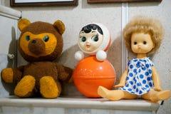 老葡萄酒儿童的玩具-一个玩偶、一头熊和一个翻转者在壁炉架 库存照片