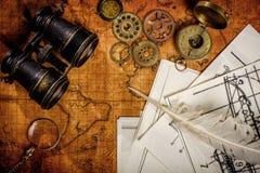 老葡萄酒减速火箭的指南针和双筒望远镜在古老世界地图 免版税库存照片