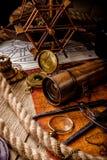 老葡萄酒减速火箭的指南针和小望远镜在古老世界地图 图库摄影