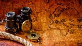 老葡萄酒减速火箭的指南针和小望远镜在古老世界地图 库存图片