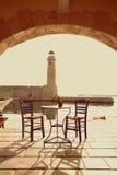 老葡萄酒咖啡馆和灯塔在海Rethymnon 免版税库存图片