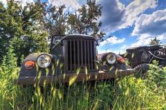 老葡萄酒在自然本底的所有轮子推进汽车前面与绿草、树和蓝天 库存图片