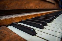 老葡萄酒多灰尘的钢琴钥匙 库存照片