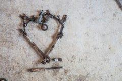 老葡萄酒工具和零件在爱心脏形状的混凝土平展放置了 免版税库存照片