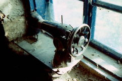 老葡萄酒手缝纫机 肮脏,在窗台的立场 图库摄影