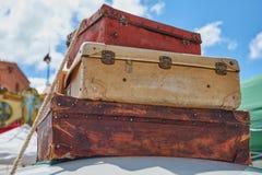 老葡萄酒旅行手提箱特写镜头紧固了到一辆汽车的屋顶有绳索的和在背景中与分类的可爱的蓝天 免版税图库摄影