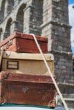 老葡萄酒旅行手提箱特写镜头紧固了到一辆汽车的屋顶有绳索的和在背景中塞戈维亚渡槽, 免版税库存照片