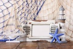老葡萄酒木白色框架、灯塔、海星和帆船在木桌上 葡萄酒被过滤的图象 船舶生活方式 免版税库存照片