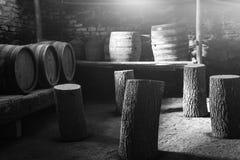 老葡萄酒桶在一个老地窖里,黑白的 免版税库存图片