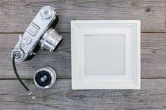 老葡萄酒照相机、透镜和白色空的框架在木backg 图库摄影