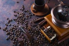 老葡萄酒研磨机用烤咖啡豆和研磨咖啡在石背景 免版税库存图片