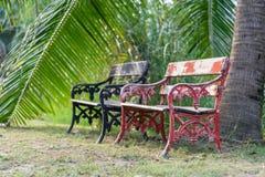 老葡萄酒红色和黑长木凳在公园 库存图片