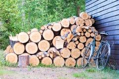 老葡萄酒自行车和切好的木头 免版税图库摄影