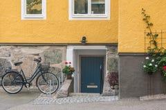 老葡萄酒自行车的图片在木门前面的在街道 免版税库存照片