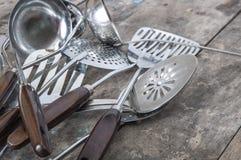 老葡萄酒金属汤杓子和开槽的匙子 免版税库存图片