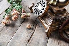 老葡萄酒黑色转台式电话和玫瑰花束在木背景的 库存图片