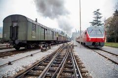 老蒸汽火车和新的电车 免版税库存照片