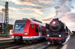 老蒸汽火车和现代电车在种族 库存照片
