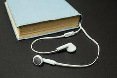老蓝皮书和白色耳机在黑背景 库存照片