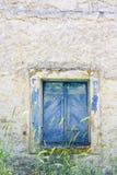 老蓝色在难看的东西墙壁上的被绘的窗口 库存照片