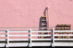 老蓝色梯子站立对桃红色灰泥墙壁 库存图片