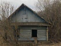 老蓝色毁坏了木头木被放弃的被破坏的蓝色打破的农村房子与残破的窗口的 免版税库存照片