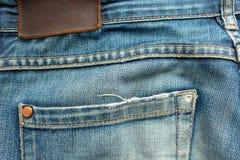 老蓝色牛仔裤后面有口袋和一个皮革标记的 特写镜头照片 库存照片