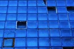 老蓝色玻璃打破的瓦片墙壁在大厦的 抽象负面因素 库存图片