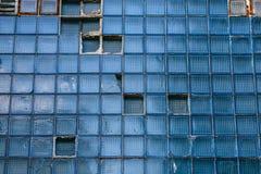 老蓝色玻璃打破的瓦片墙壁在大厦的 抽象负面因素 免版税库存图片