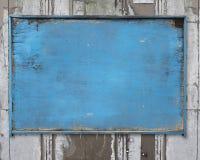 老蓝色空白风化了在粗砺的肮脏的墙壁上的木noticeboard 图库摄影