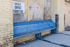 老蓝色长凳外部在市内贫民区放弃了砖仓库 免版税图库摄影